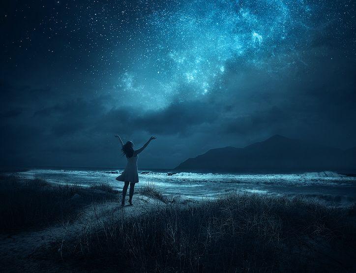 девочка поднимает руки к звездному небу
