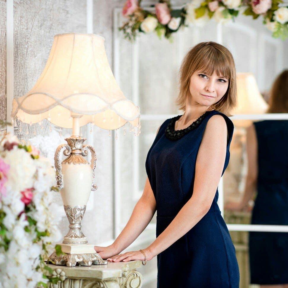 Маргарита Солнечная возле настольной лампы в темно синем платье