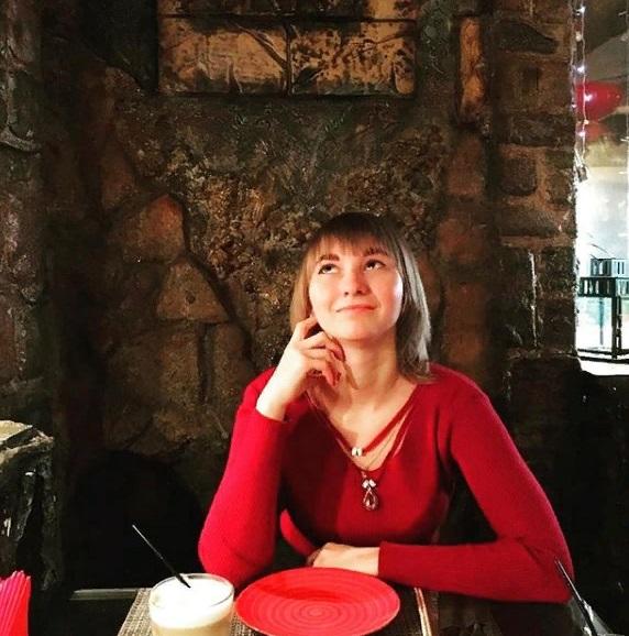 Психолог Маргарита Солнечная смотрит вверх девушка за столом в красном свитере